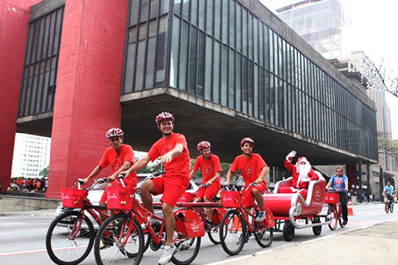 Trenó conduzido por ciclistas percorre o Natal Iluminado na avenida Paulista, em São Paulo.