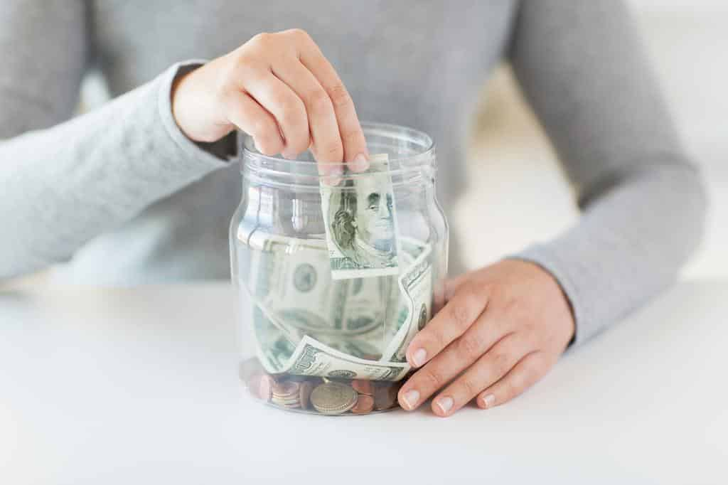 A woman putting money into a jar from having earned money from a referral to OhmConnect