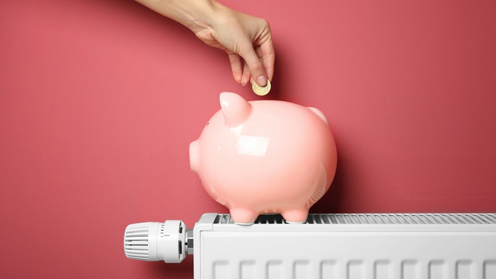 A hand putting money into the piggy bank illustrating how much you can earn with OhmConnect