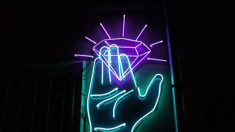 Diamond status of OhmConnect portrayed by a neon sign hand holding a diamond