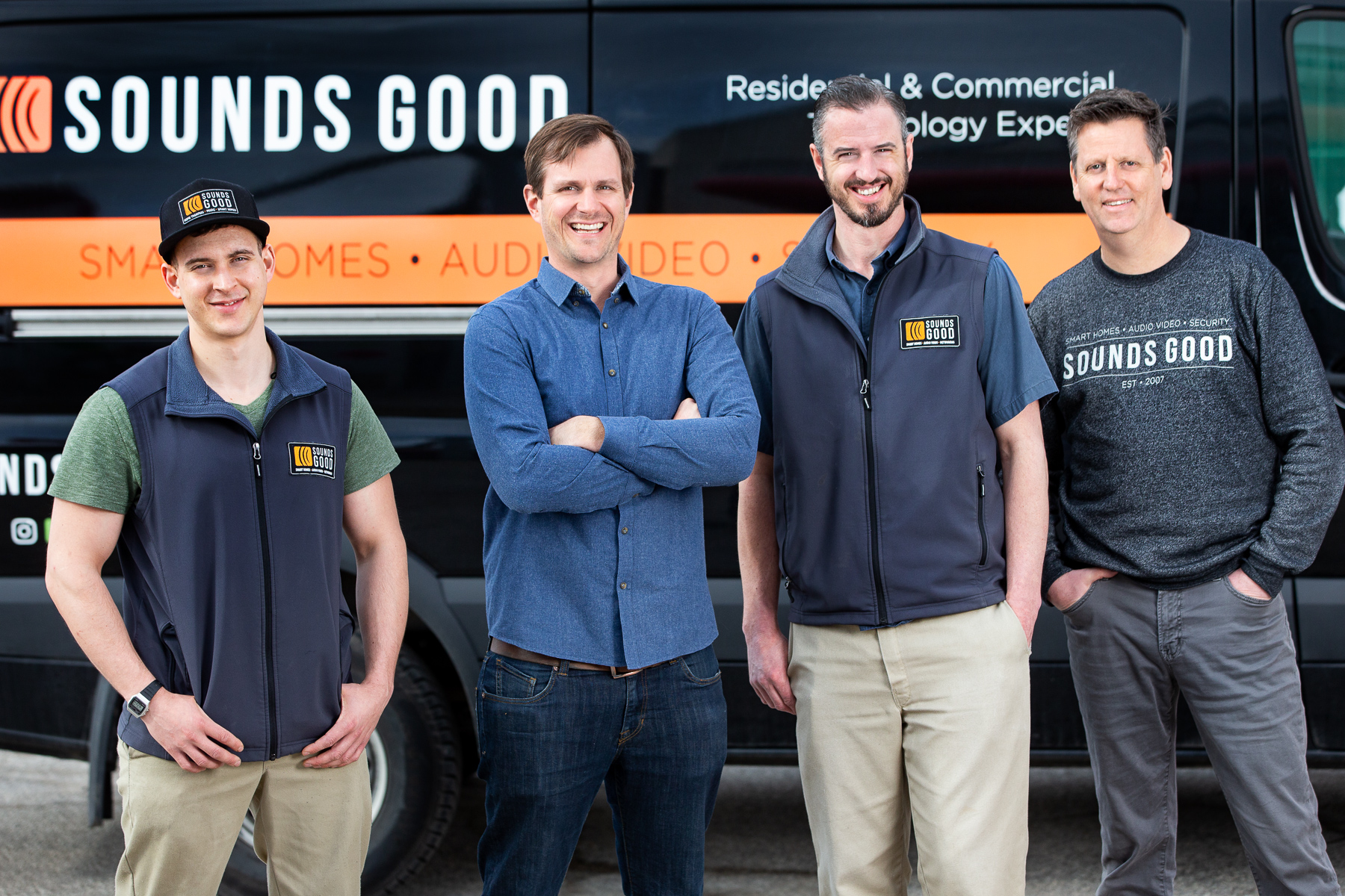 Photograph of the Sounds Good Smart Homes Team members standing in front of one of their fleet vehicles.