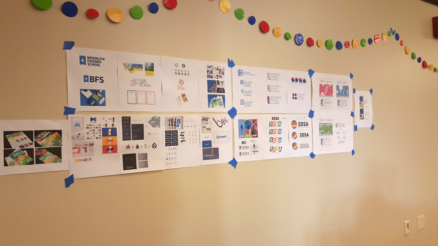 design comps on the wall for client review.