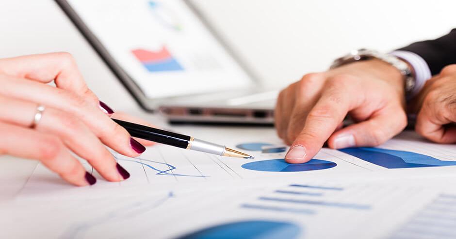 imagem de duas mãos analisando gráficos em papel