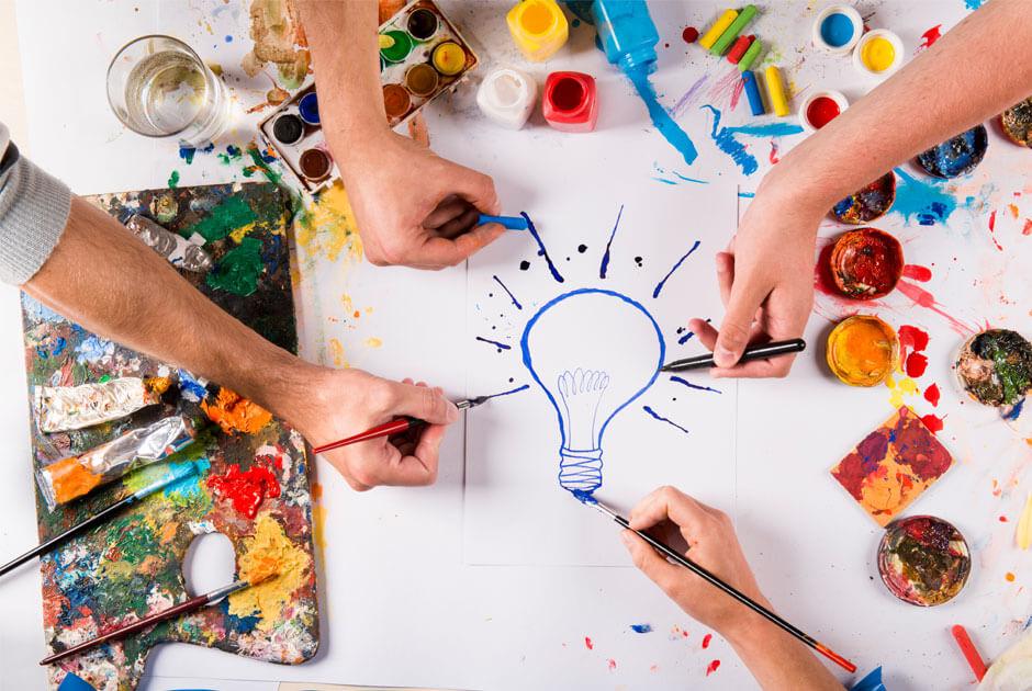 imagem de quatro mãos desenhando uma lâmpada azul