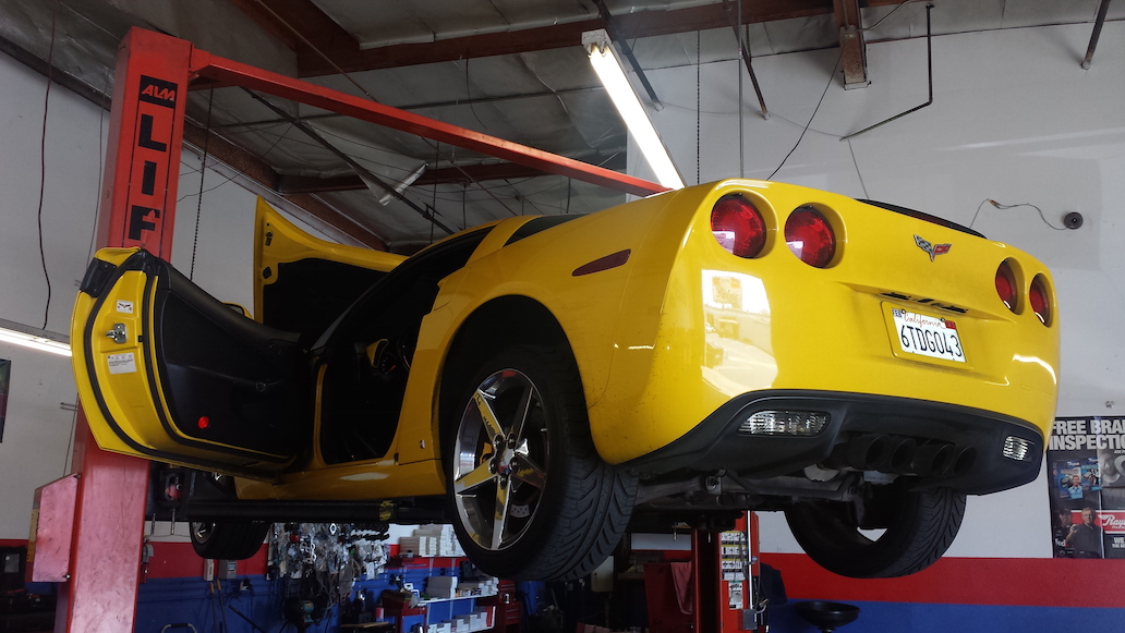 corvette being serviced in lift in alonso's auto repair