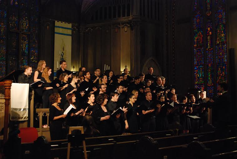 Image of CAC's first concert - choir members in black clothing on stage.