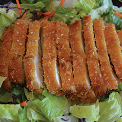 picture of crispy chicken salad drizzled with our tangy house vinaigrette