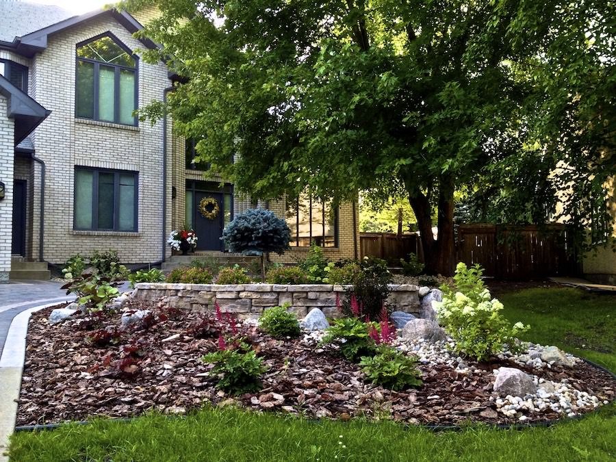 Front yard landscaping in WInnipeg with bark mulch and retaining wall
