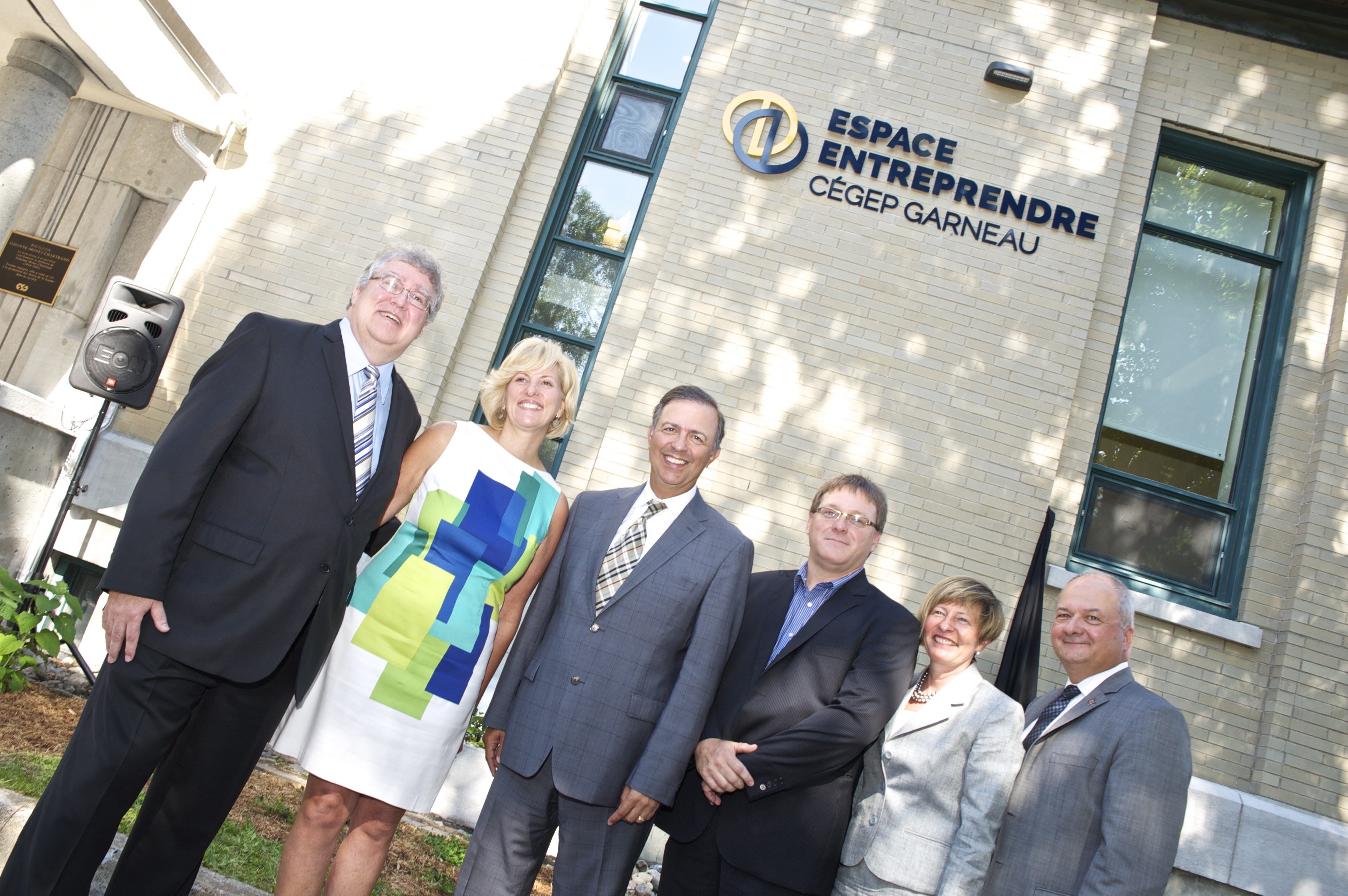 Six people smiling on camera in front of Garneau's L'Espace Entreprendre CEGEP.