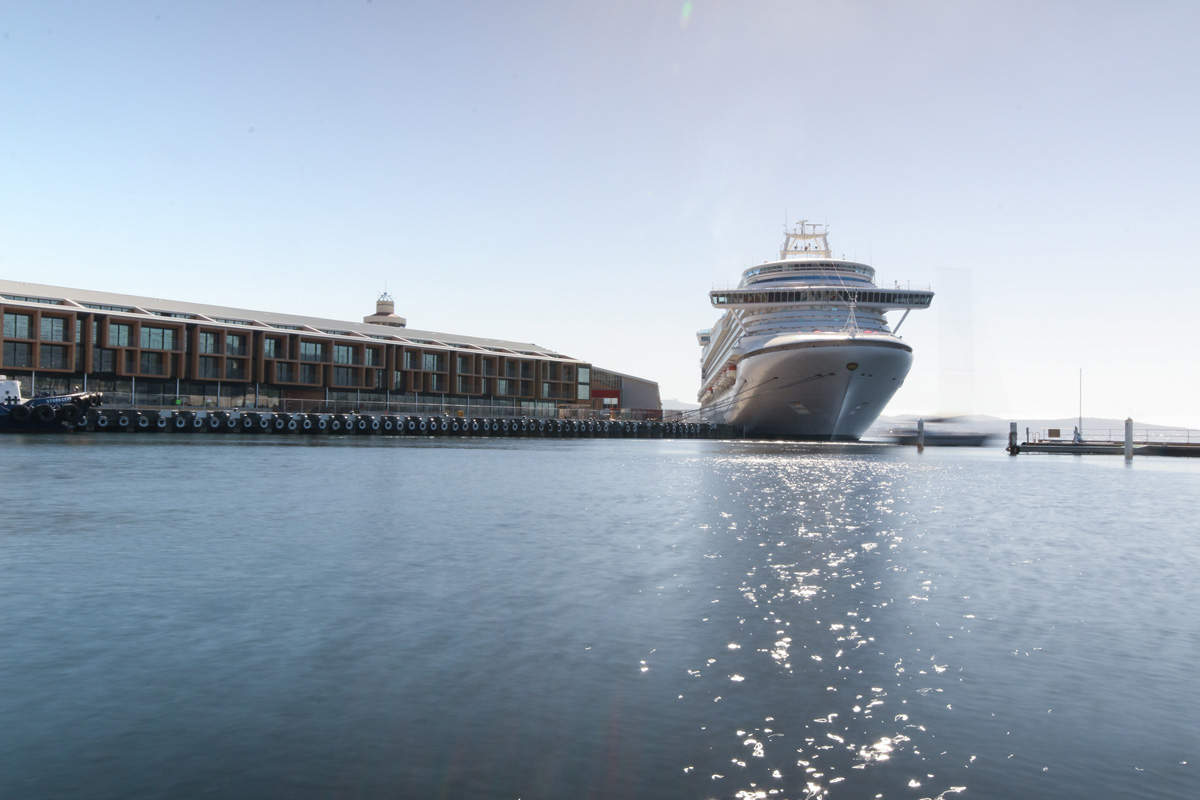 The cruise shop docked in at Hobart as a sailing boat passes by.