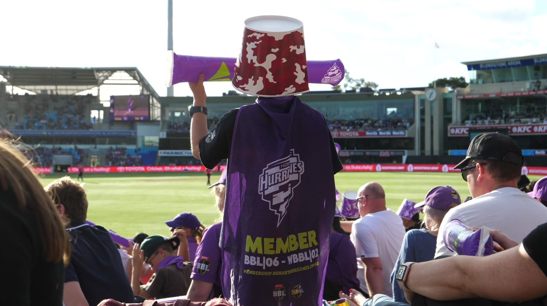 Child standing watching big bash game