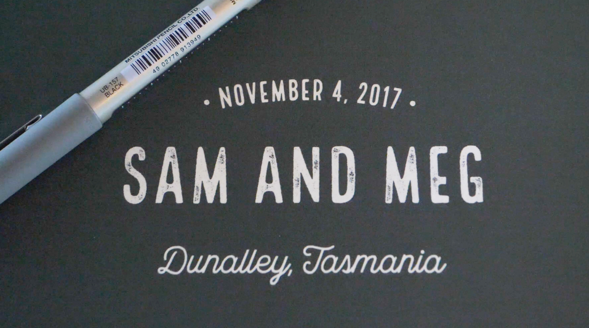 The cover of their wedding book that says Sam and Meg
