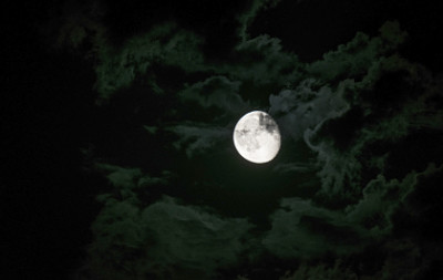 A full moon peeking from behind a cloud in a dark sky.