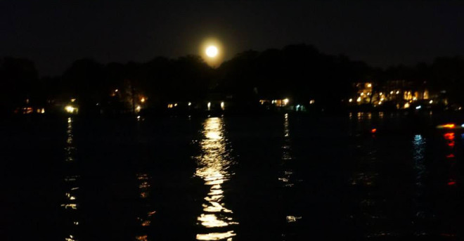 Moonlight glimmering over the water of Lake Maitland. Spot-lit houses along the shore casting warm glowing light.