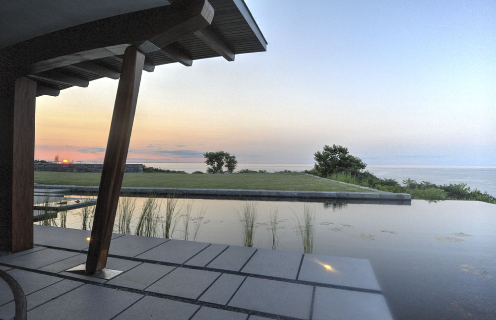 Sunset over a terrace, infinity edge pool, naturally filtered pool