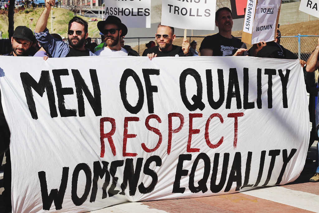 """Men holding a sign that says """"Men of quality respect women's equality"""""""