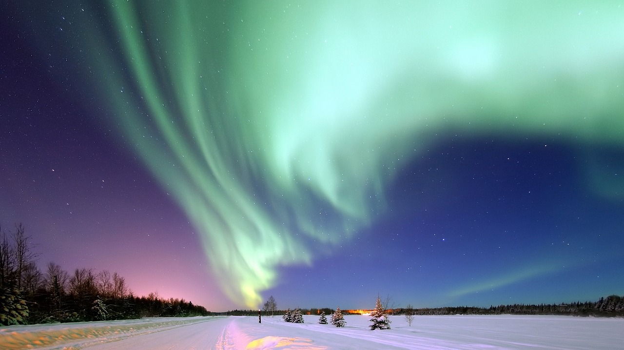 The swirl of the Aurora Borealis over a winter landscape with blue, green and purple tones throughout