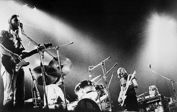 David Gilmore playing guitar, Nick Mason playing drums, Roger Waters playing bass, and Rick Wright playing keyboard on stage together as Pink Floyd.
