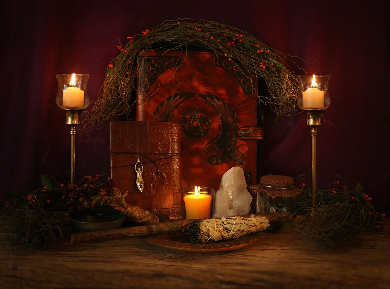 Altar with 2 candles burning with spell book, journal, large crystal and sage in between them.