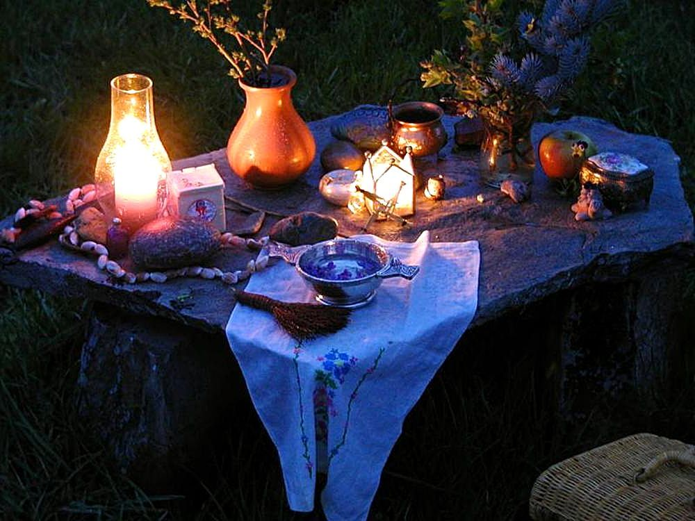 Altar in the dark with candle, vases with herbs and plants, talisman, shells, fruit, small broom and bowl of water with flower petals.