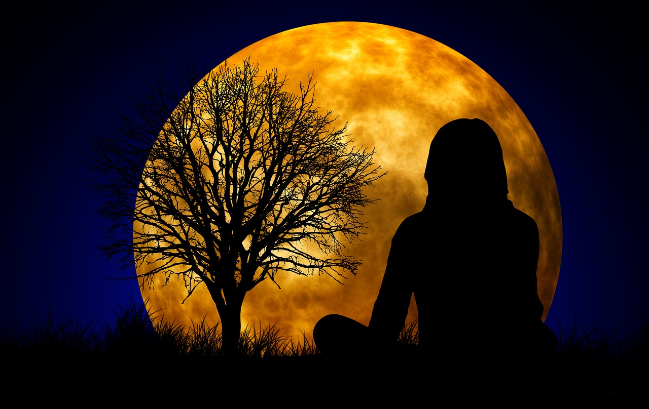 Silhouette of women sitting in front of a full moon