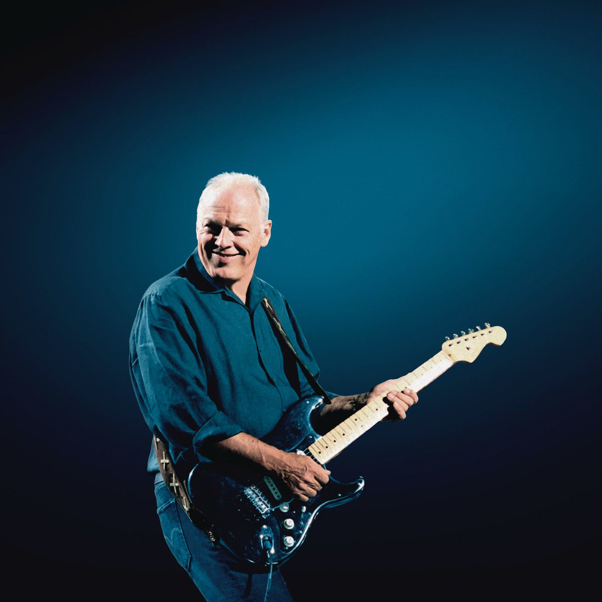 David Gilmour in front of a blue background, smiling and playing his signature black Fender Stratocaster