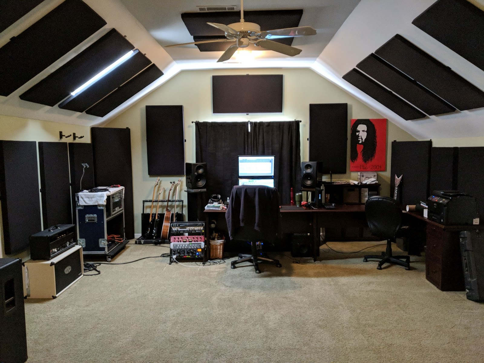 A picture of a home studio with computers, speakers, guitars, and guitar amps.