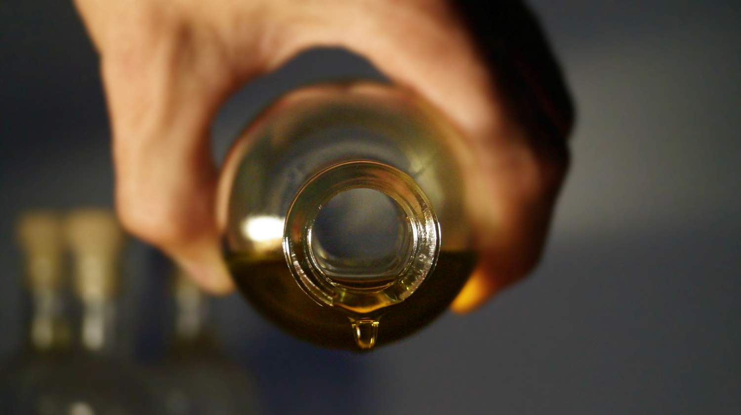 Hand holding a sideways bottle with oil hanging over the side