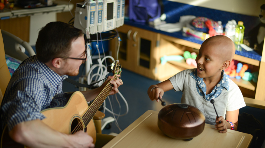 A music therapist plays guitar with a patient who is playing a percussion instrument.