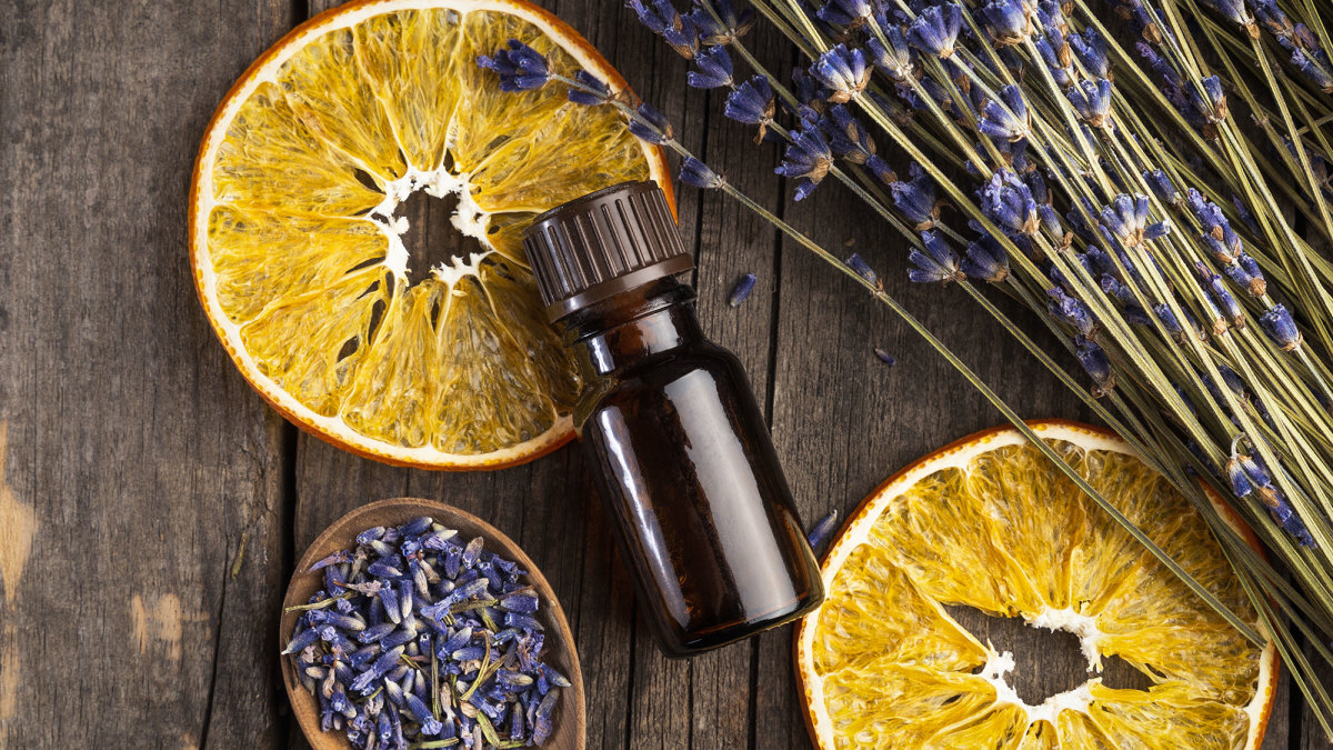 dry oranges and lavender pedals on wood with essential oil bottle laying on top