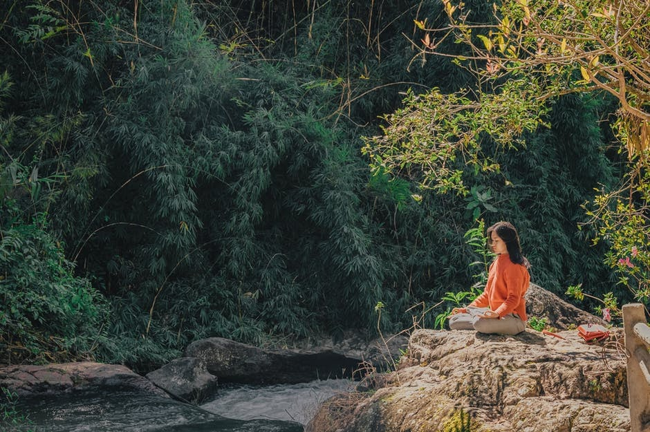 Woman meditating near a stream