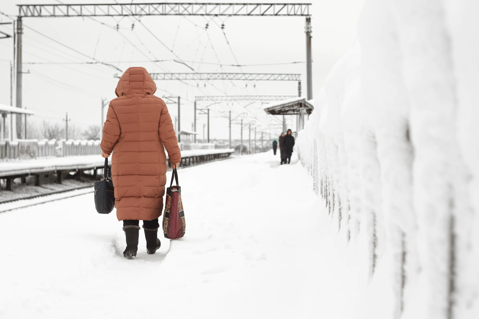 Woman walking in snow near train tracks