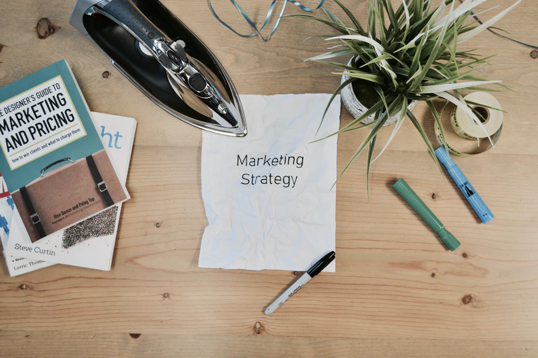 """Table cluttered with books and a paper that says """"marketing strategy"""""""