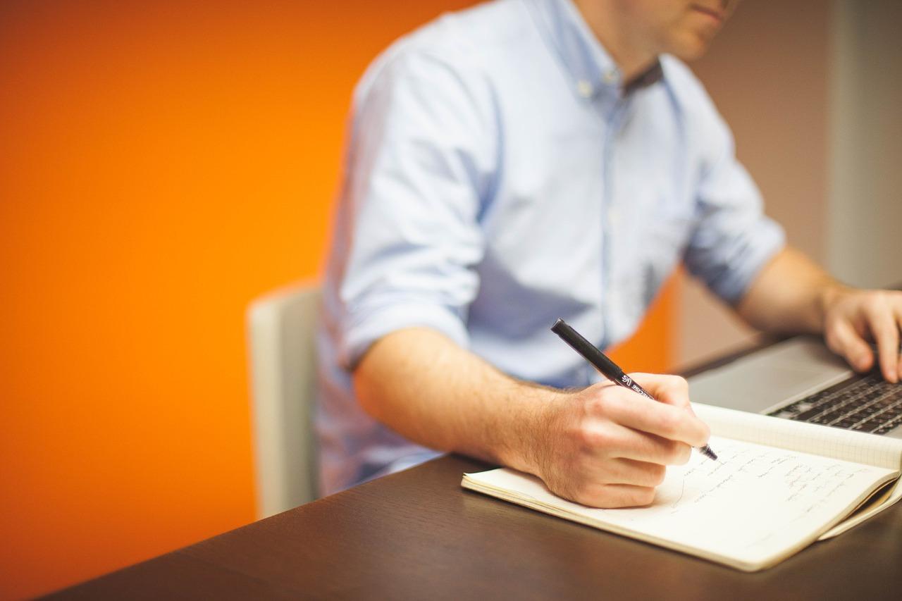 Man using laptop and writing