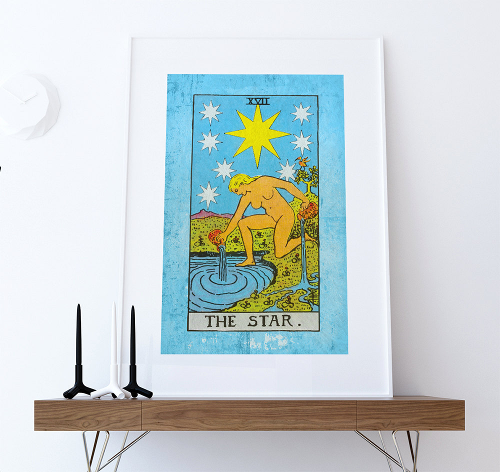 A large print of the star tarot card hung in a frame on a white wall