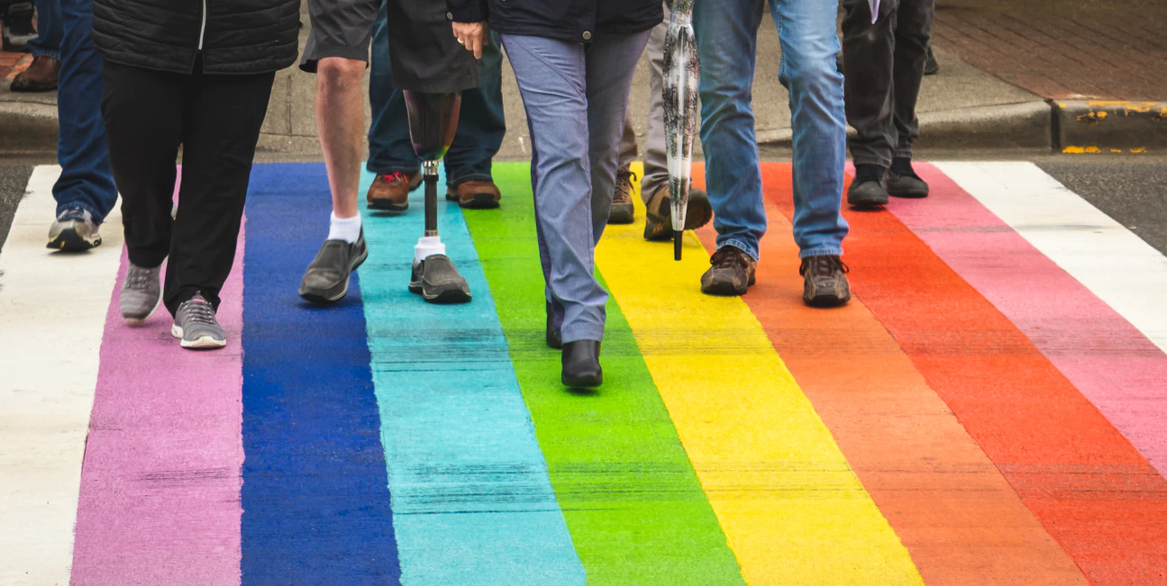 Various pairs of legs, presumably belonging to people of various genders and ethnicities, and at least one featuring a prosthetic, walk alone a rainbow-striped crosswalk.