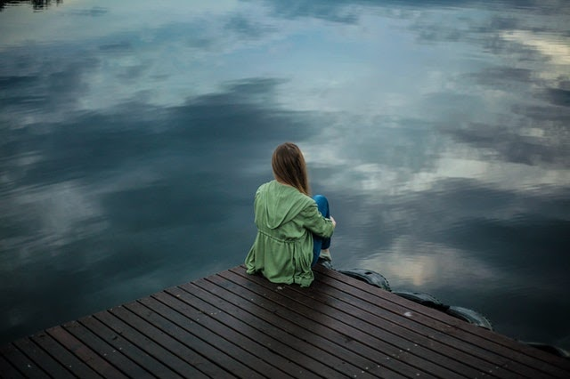 Girl sitting on dock looking out to a lake with her back towards the camera