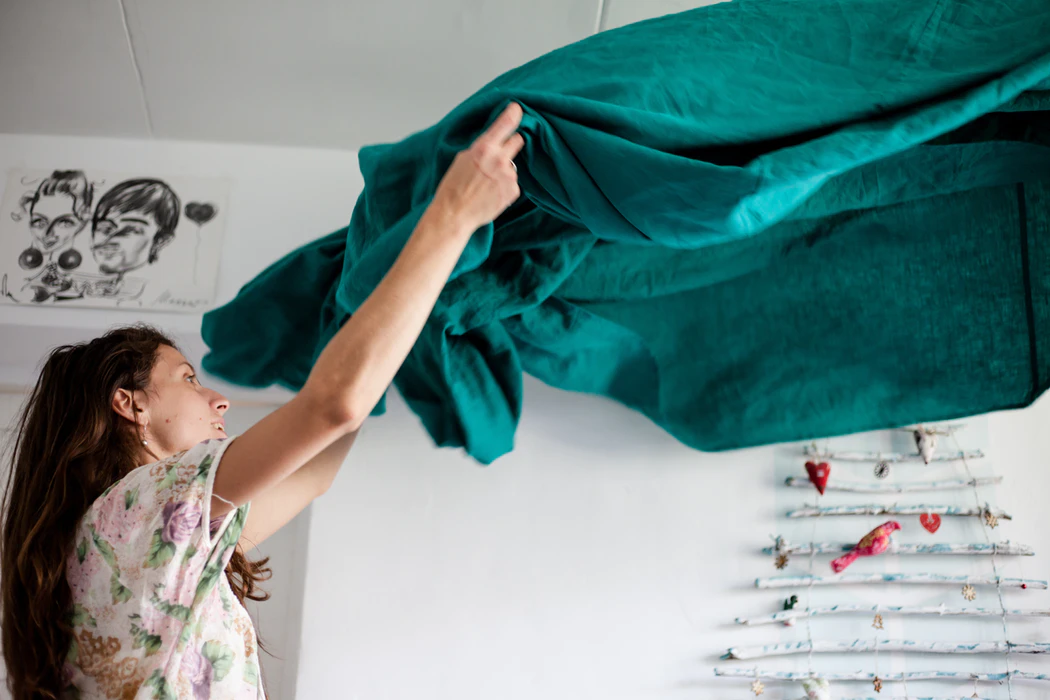 Woman shaking out dark turqoise tablecloth