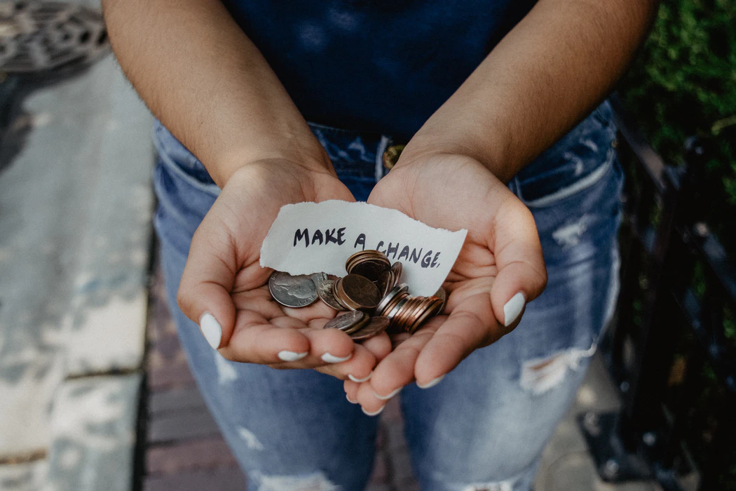 """Cupped palms holding spare change and a piece of paper on which is written """"MAKE A CHANGE"""""""
