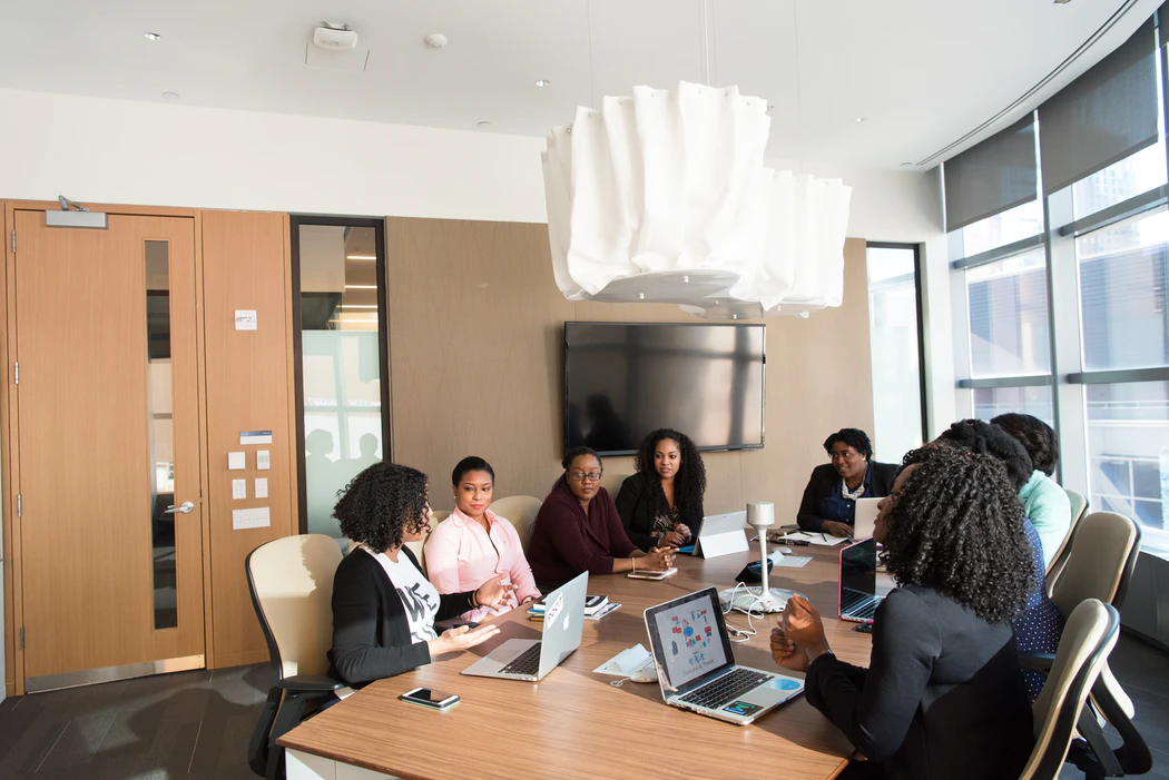 Conference table filled with black women at a usiness meeting