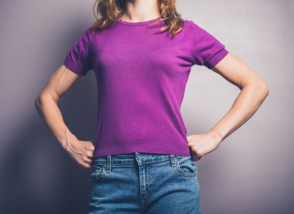 picture of woman from upper legs to neck wearing a purple shirt and starting with her fists on her hips