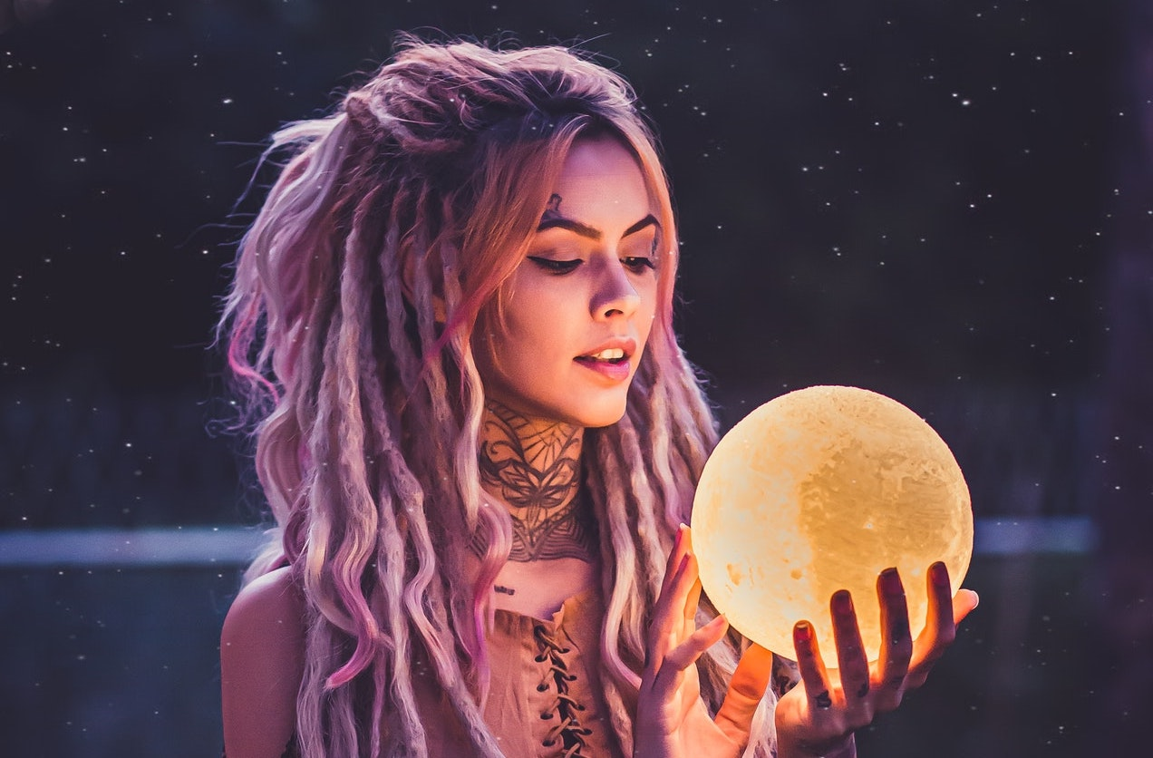 a woman with long hair holding the moon