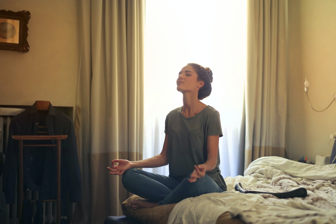 A woman on her bed in a meditation posture with her eyes closed