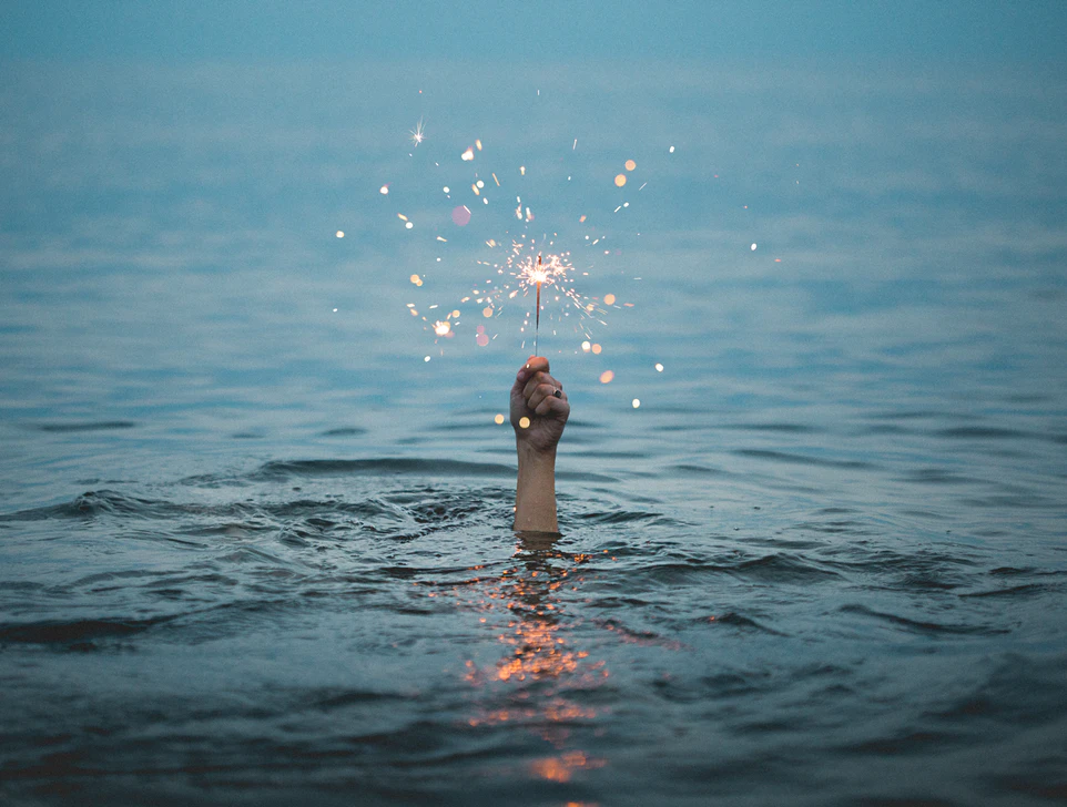 In the middle of a body of water, a single hand pokes up. It has a ring and is holding a lit sparkler.