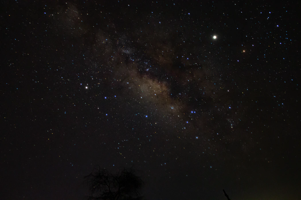 Image of the night sky featuring a glimpse of the milky way and a distance, bright spot, presumably Uranus