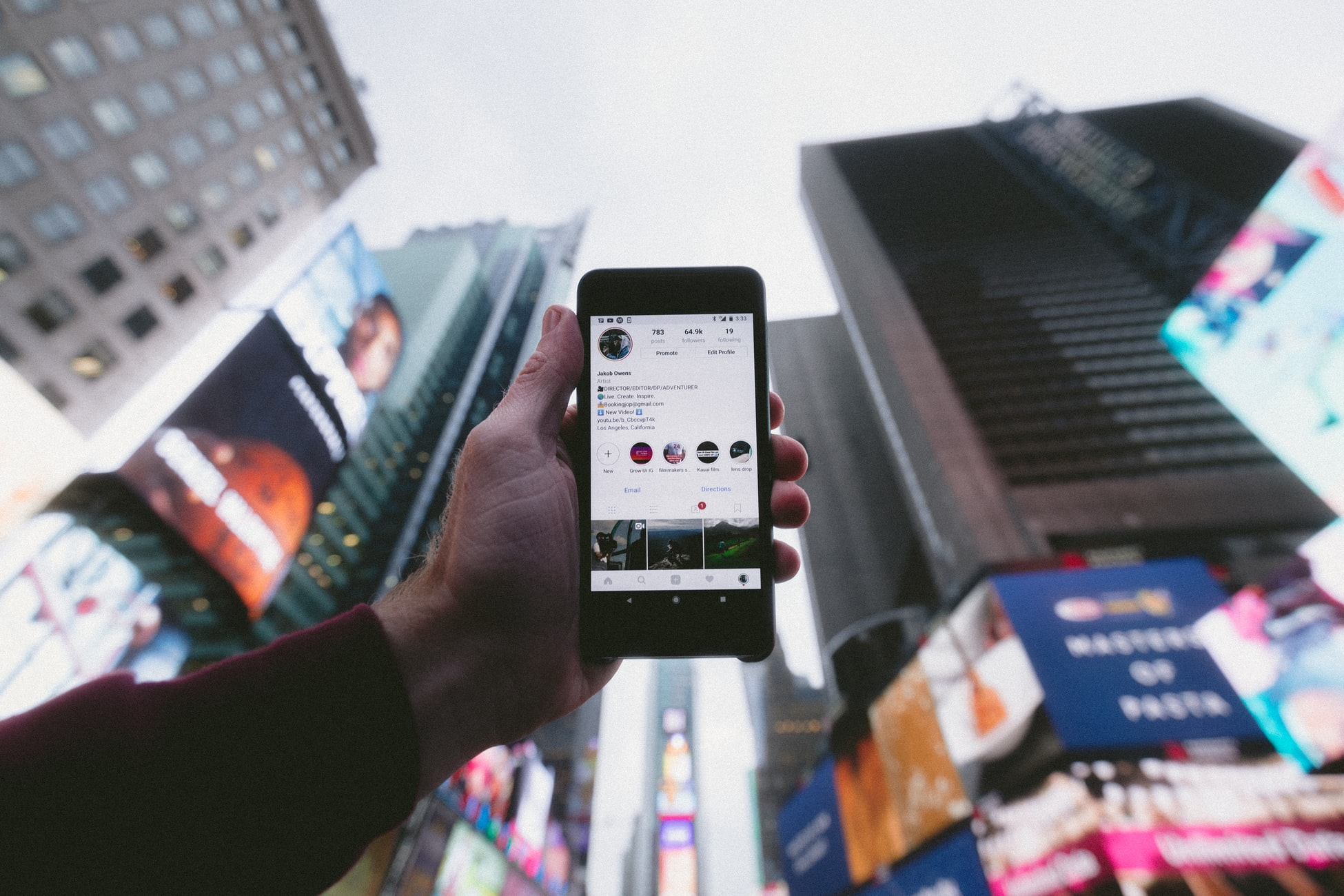 person holding a phone with social media pulled up in times square