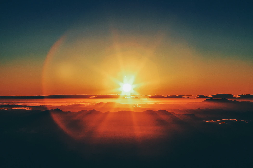 A bright sunrisewith an orange circle of lense flare around the sun
