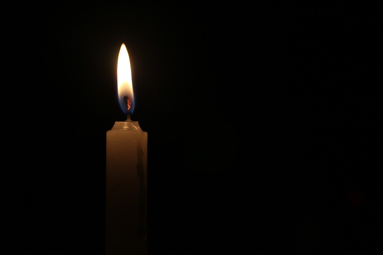 A burning candle in the dark.