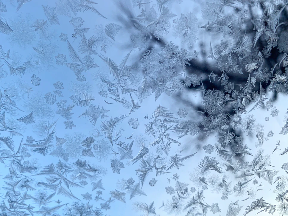 A close up of ice patterns on a windshield