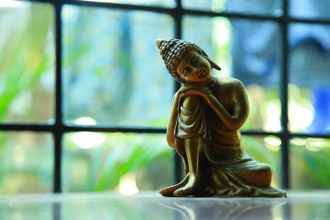 Small statue of the Buddha in front of a window